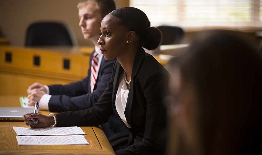 Woman in a suit sitting and taking notes in a court