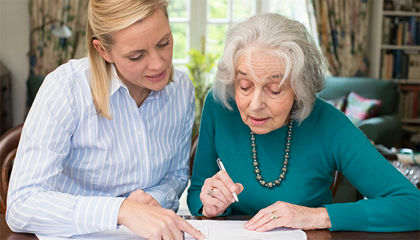 Woman helping an elder with paperwork