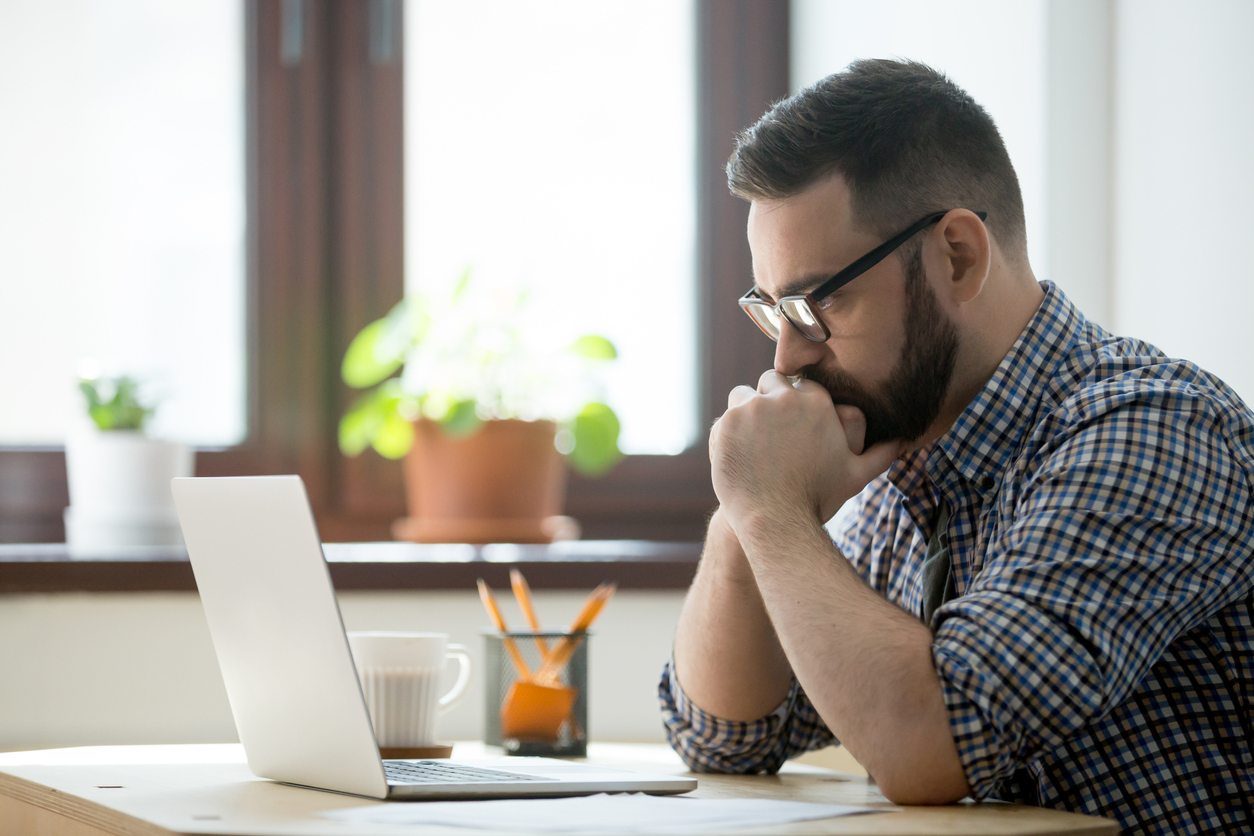 Man contemplatively looking at his laptop