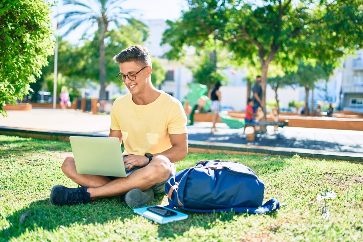 Smiling undergraduate student sitting in the grass on campus with his laptop